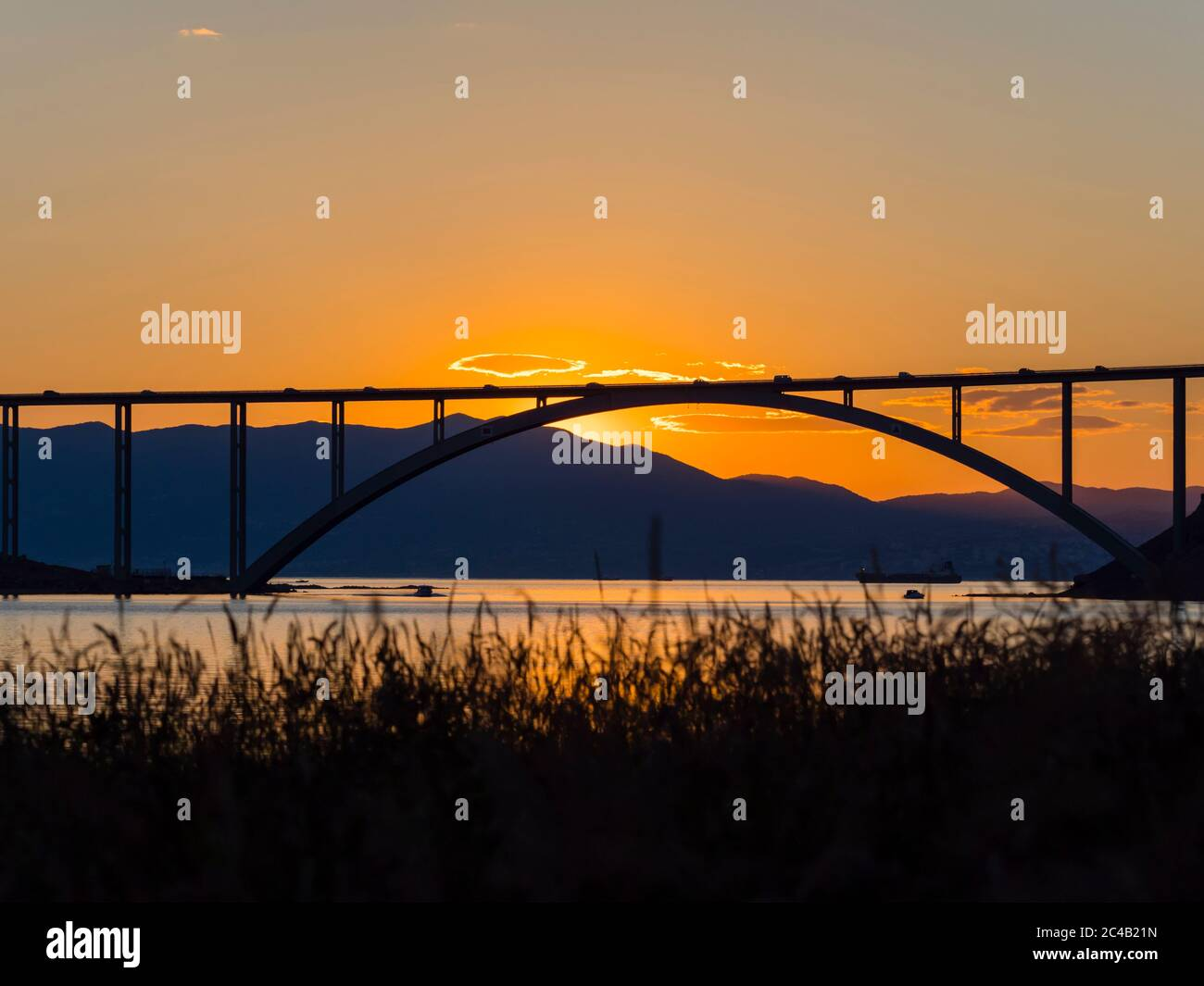 Sunset landscape silhouette silhouetting grass in foreground bridge mainland to island Krk Croatia Stock Photo
