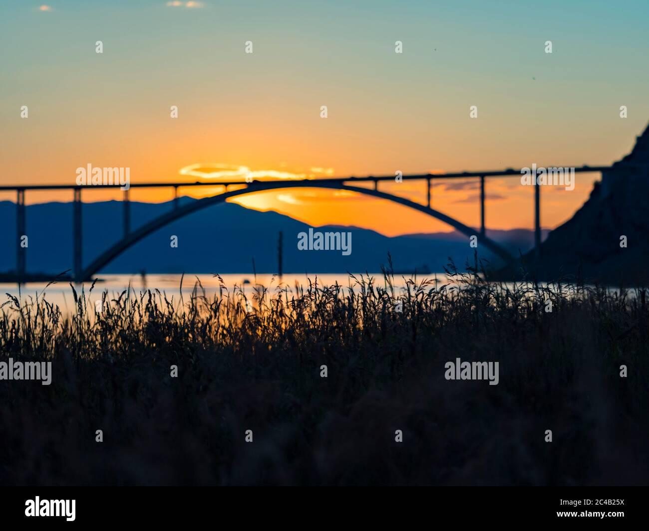 Sunset landscape silhouette silhouetting grass in foreground bridge mainland to island Krk Croatia Stock Photo