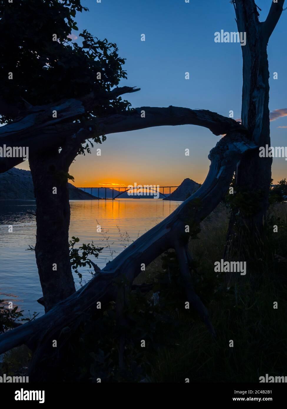 Sunset landscape silhouette silhouetting trees framed bridge mainland to island Krk Croatia Stock Photo