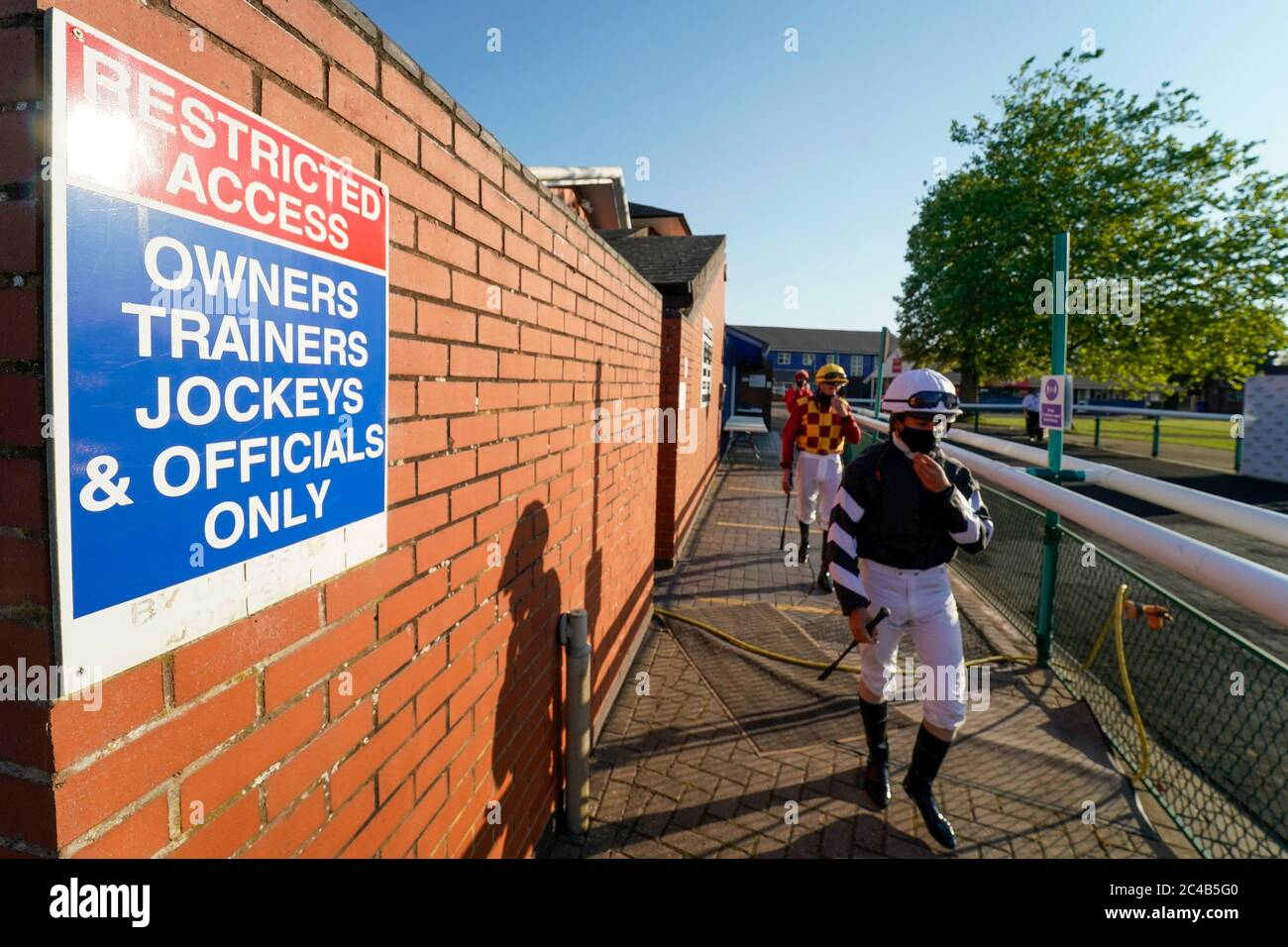 A general view as jockeys leave the weighing room and make their way to the parade ring at Leicester Racecourse. Stock Photo