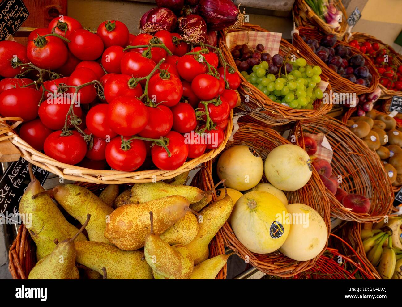 Fresh fruit and vegetables displayed in baskets outside an Italian greengrocers. Stock Photo