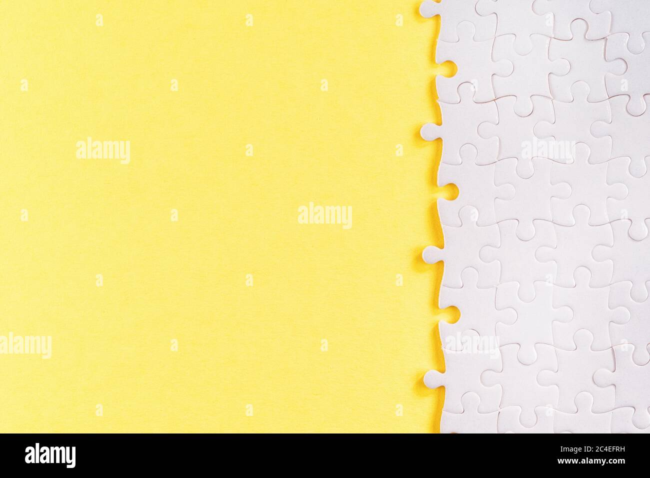 White jigsaw puzzle pieces on yellow. Abstract template and background with copy space Stock Photo