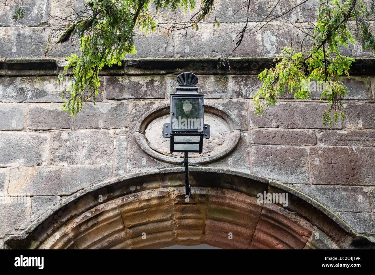 rought Iron decorative lantern seen at the entrance to an old, medieval building. A new style, energy efficient bulb is seen within the lantern itself Stock Photo