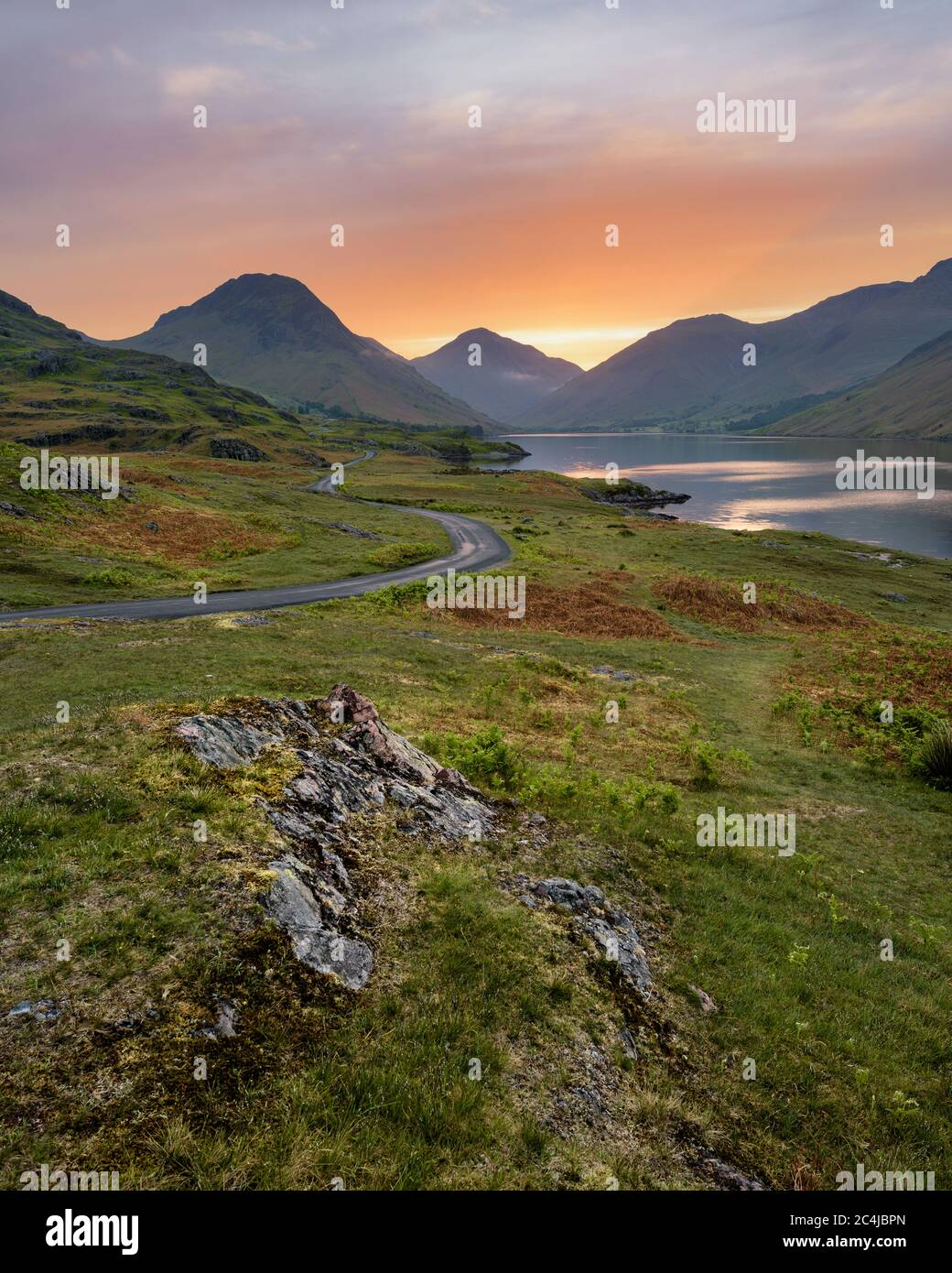 Winding Single Track Road Leading Through Green Secluded Countryside With Beautiful Sunrise. Wastwater, Lake District, UK. Stock Photo