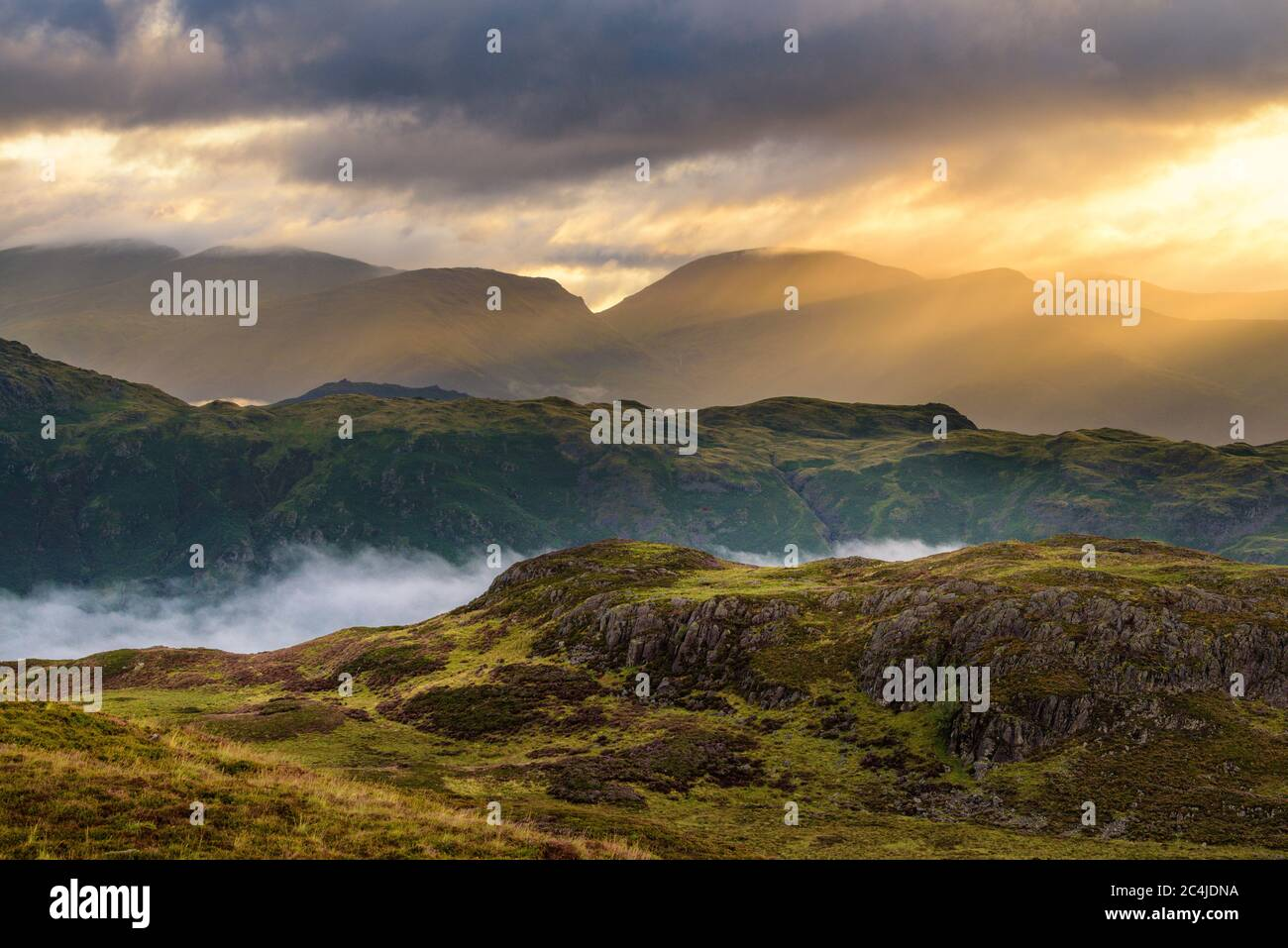 Beautiful Golden Rays Of Sunlight Breaking Through Clouds On A Misty Morning In The English Lake District. Stock Photo