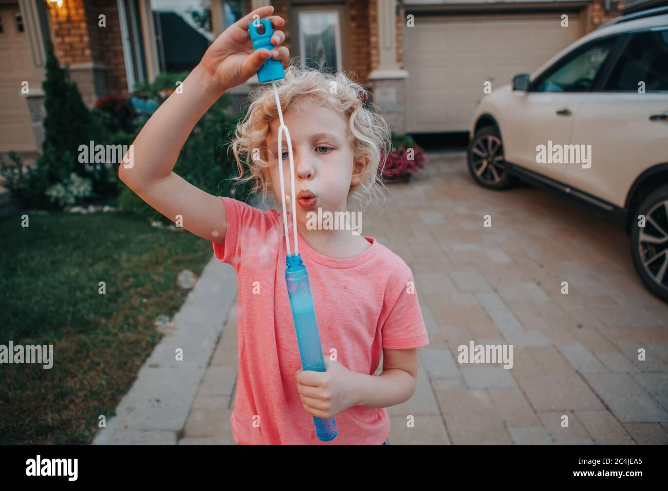 Young Caucasian girl blowing soap bubbles on home front yard. Child having fun outdoor on sunset. Authentic happy childhood magic moment. Stock Photo