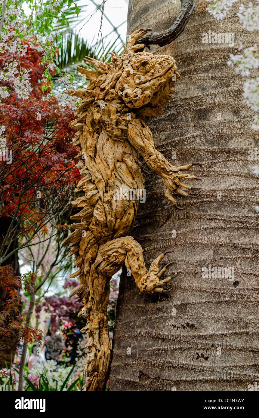 Wood carving of a lizard in Singapore Gardens by the Bay flower dome Stock Photo