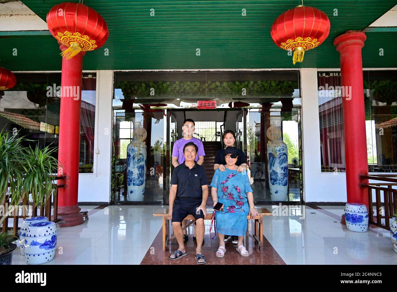 (200628) -- NANCHANG, June 28, 2020 (Xinhua) -- Zhu Yicai (L,front) poses for a photo with his family at his farmhouse in the Poyang Lake scenic area in Yugan County, east China's Jiangxi Province, June 16, 2020. Zhu Yicai gave up his fishing business in 2012 due to the worsening aquatic environment in the Poyang Lake. In 2018, Zhu was running a family farm when he noticed that lots of tourists came to the lake to watch migratory birds. Zhu then captured the business opportunity and opened a 1,800-square-meter farmhouse, which can accommodate more than 200 people dining at the same time. China Stock Photo