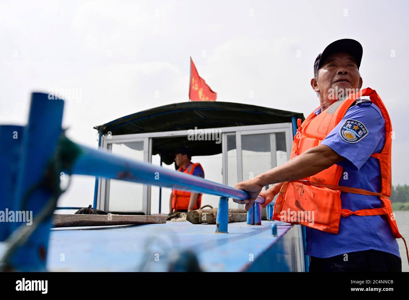 (200628) -- NANCHANG, June 28, 2020 (Xinhua) -- Wu Houchun, an ex-fisherman who works at a Yangtze finless porpoise protection team, takes part in a patrol mission on the Poyang Lake in Hukou County, east China's Jiangxi Province, June 8, 2020. Eight of the 11 team members are fishermen-turned finless porpoise protectors who patrol the Poyang Lake on a daily basis. Their missions include dismantling illegal fishing facilities and preventing unlawful activities that damage the Poyang Lake's fisheries resources. China began a 10-year fishing moratorium from the beginning of this year in 332 cons Stock Photo