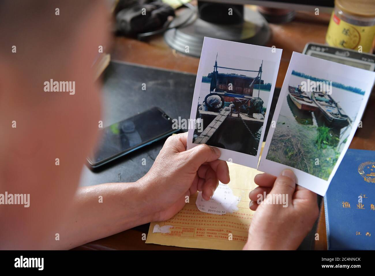 (200628) -- NANCHANG, June 28, 2020 (Xinhua) -- Wu Huashan displays photos of the fishing boats he once owned in Xiangshan Township, Nanchang, east China's Jiangxi Province, June 5, 2020.  Having learned fishing at an early age with his parents, Wu was a skilled fisherman and was head of a local fishery association. In late 2019, he bade farewell to his boats and started a crayfish business. China began a 10-year fishing moratorium from the beginning of this year in 332 conservation areas in the Yangtze River basin, which will be expanded to all the natural waterways of the country's longest r Stock Photo