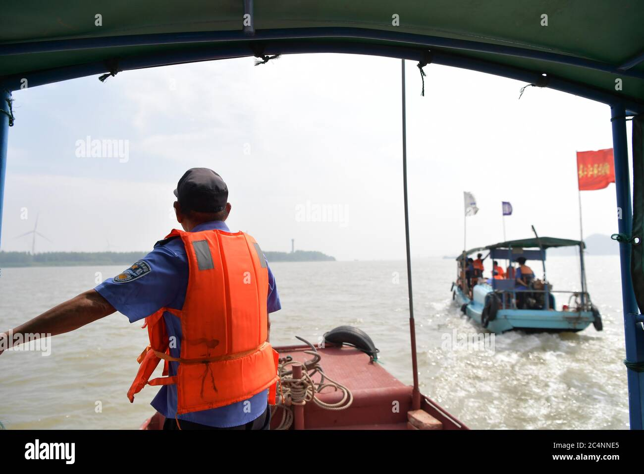 (200628) -- NANCHANG, June 28, 2020 (Xinhua) -- Members of a Yangtze finless porpoise protection team take part in a patrol mission on the Poyang Lake in Hukou County, east China's Jiangxi Province, June 8, 2020. Eight of the 11 team members are fishermen-turned finless porpoise protectors who patrol the Poyang Lake on a daily basis. Their missions include dismantling illegal fishing facilities and preventing unlawful activities that damage the Poyang Lake's fisheries resources.  China began a 10-year fishing moratorium from the beginning of this year in 332 conservation areas in the Yangtze R Stock Photo
