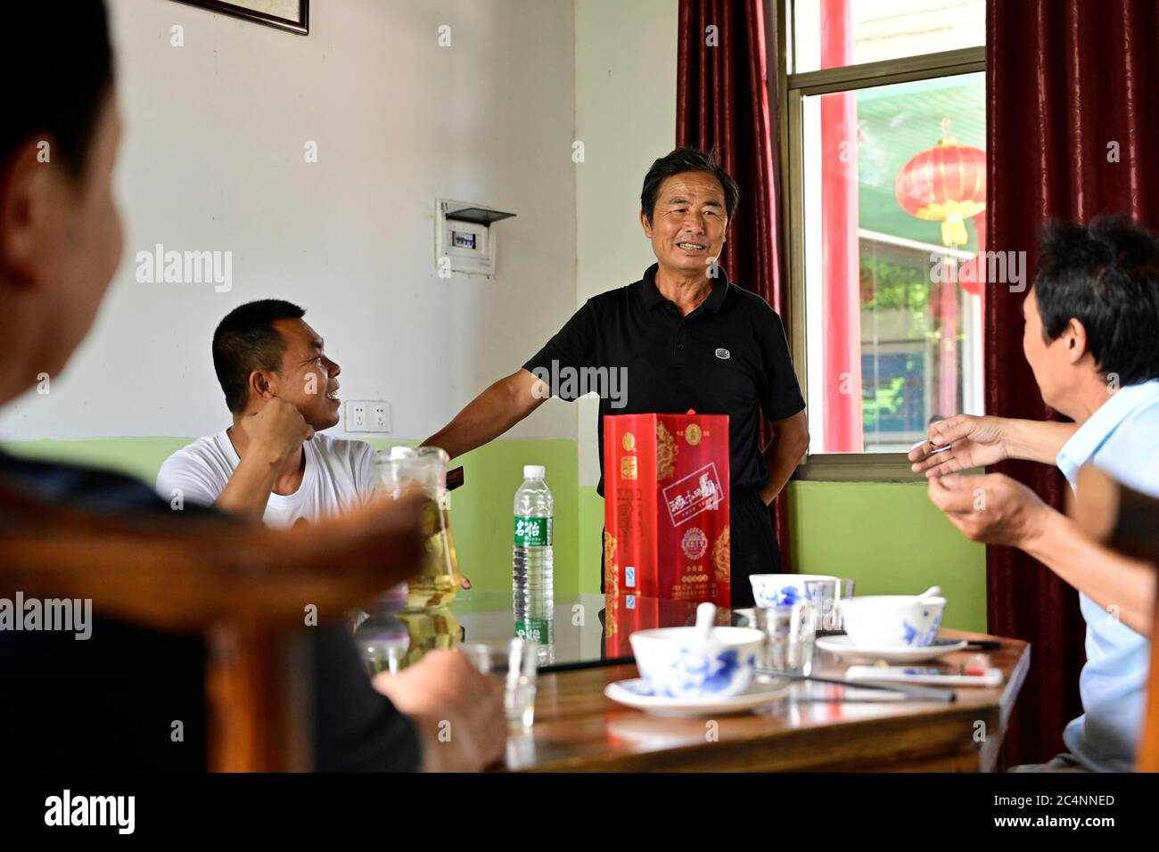 (200628) -- NANCHANG, June 28, 2020 (Xinhua) -- Zhu Yicai (C) talks to guests having a meal at his farmhouse in the Poyang Lake scenic area in Yugan County, east China's Jiangxi Province, June 16, 2020. Zhu Yicai gave up his fishing business in 2012 due to the worsening aquatic environment in the Poyang Lake. In 2018, Zhu was running a family farm when he noticed that lots of tourists came to the lake to watch migratory birds. Zhu then captured the business opportunity and opened a 1,800-square-meter farmhouse, which can accommodate more than 200 people dining at the same time. China began a 1 Stock Photo