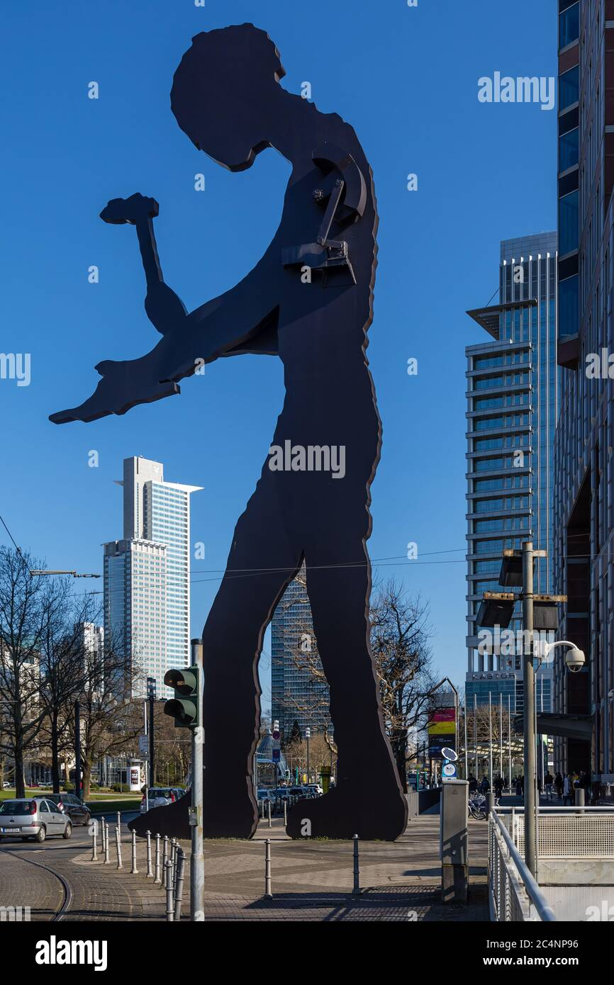 """Frankfurt, Hesse, Germany: """"Hammering Man"""" by Jonathan Borofsky, a monumental kinetic sculpture of a painted steel silhouette of a man with a hammer. Stock Photo"""
