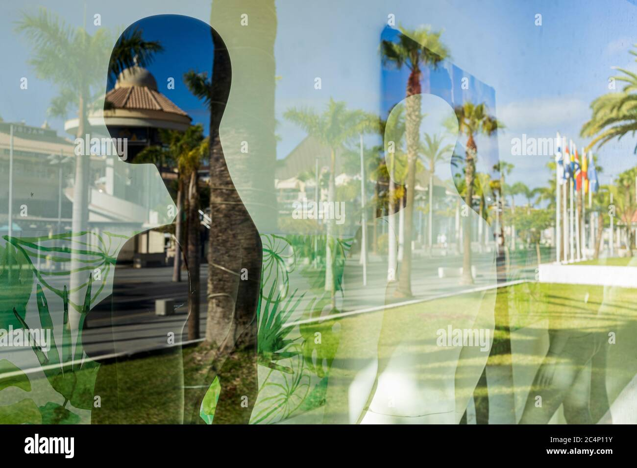 Reflections in windows along the Avenida de Las Américas, nicknamed the Golden Mile, a shoppers paradise in Playa de Las Americas, in a time of practically zero tourism with hotels still closed, most shops and restaurants shut, a few that are open struggling to attract some local residents. Playa de Las Americas, Tenerife, Canary Islands, Spain. 27 June 2020. Stock Photo