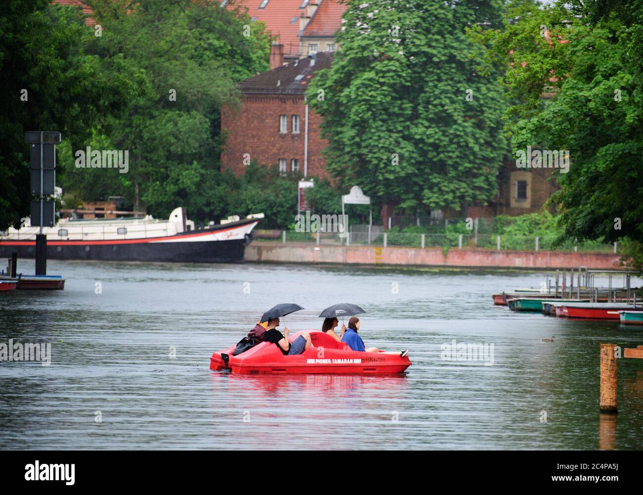 "Berlin, Germany. 28th June, 2020. Four young people ride under two umbrellas on a pedal boat in Köpenick in front of the backdrop of the event ship ""Ars Vivendi"" in the rain over the Alte Spree. Credit: Soeren Stache/dpa-Zentralbild/dpa/Alamy Live News Stock Photo"