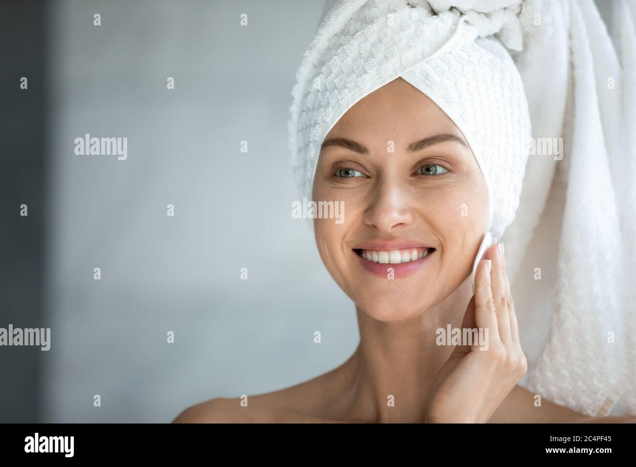 Smiling young woman look in mirror do facial beauty procedures Stock Photo