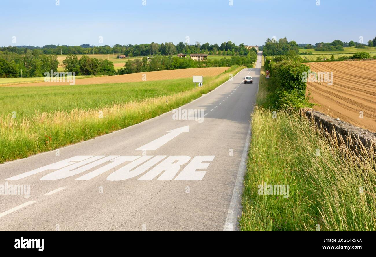Country road among hills with sign on asphalt indicating the driving direction toward the future Stock Photo