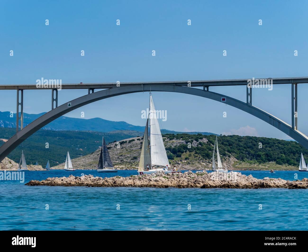 Sailboats vessel boat ship under sail behind small island near bridge Krk in Croatia Europe Stock Photo