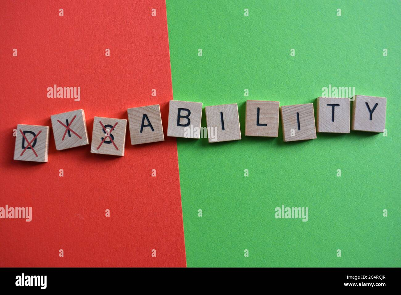 Disability, word in 3d wooden alphabet letters on a multi coloured background with Dis crossed out to leave the word Ability Stock Photo