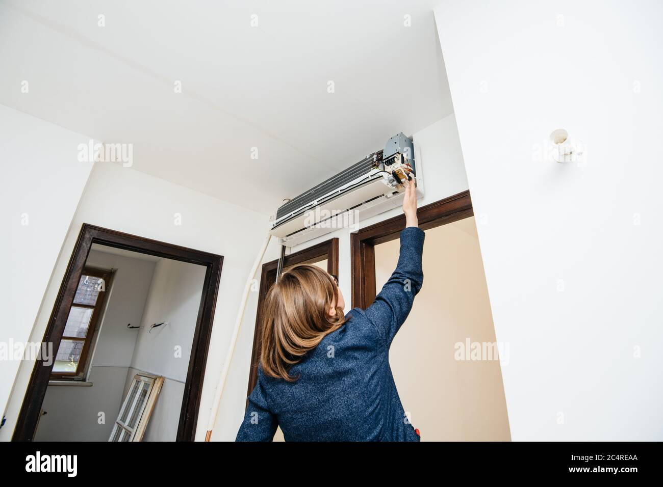 Rear view of engineer woman testing measuring trying to repair newly installed air conditioner wall ac unit Stock Photo