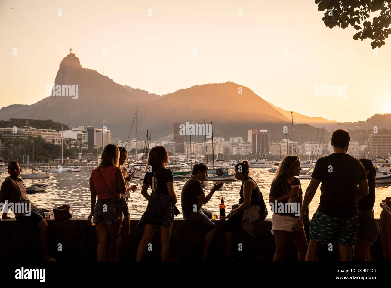 Beautiful view to Urca ocean shore with people socializing by the sunset and Corcovado mountain on the back, Guanabara Bay, Rio de Janeiro, Brazil Stock Photo