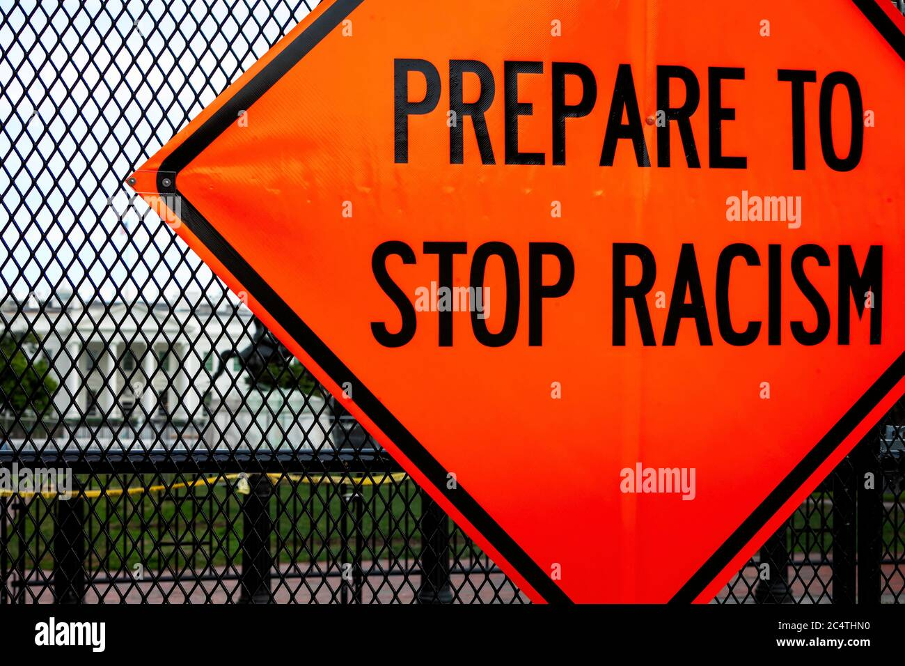 """A road construction style sign reading """"Prepare to stop racism,"""" hangs on fence at Lafayette Square / White House, Washington, DC, United States Stock Photo"""
