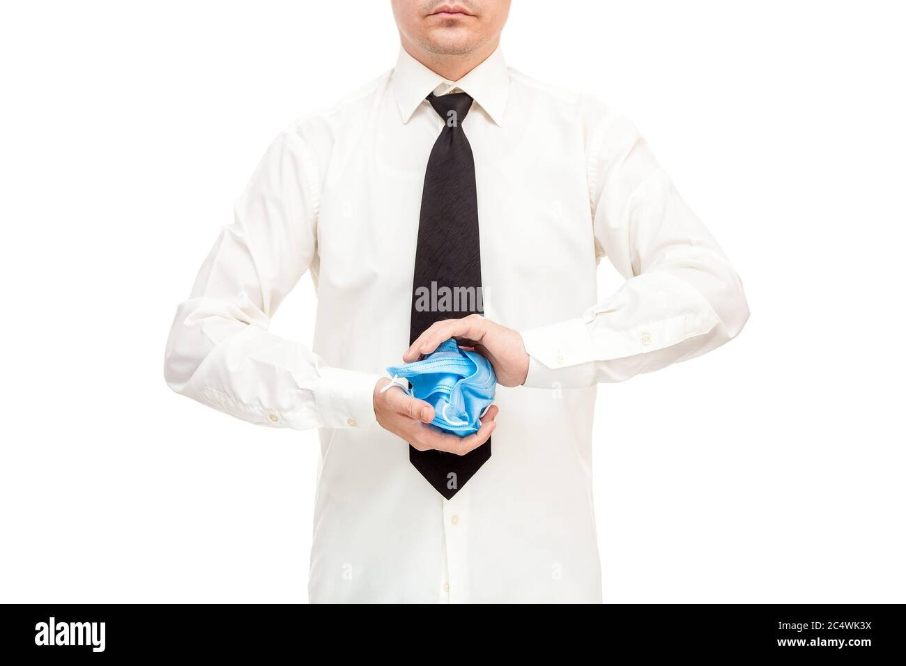 faceless man in white shirt and black tie crumpled bunch of ineffective and useless medical masks in his hands in protest against the quarantine crisi Stock Photo