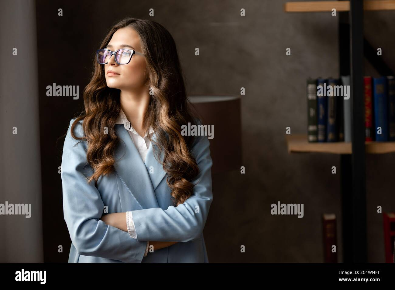 Portrait of amazing young business woman in blue glasses in the office. Stock Photo