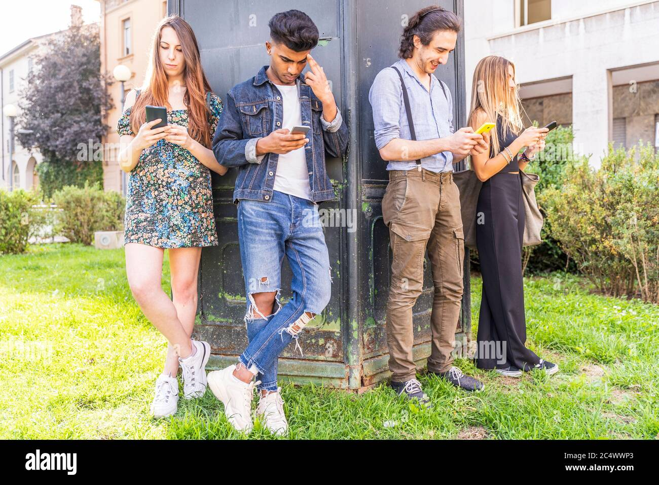 group of multiracial friends in front of a wall using smartphones to share content on social networks Stock Photo
