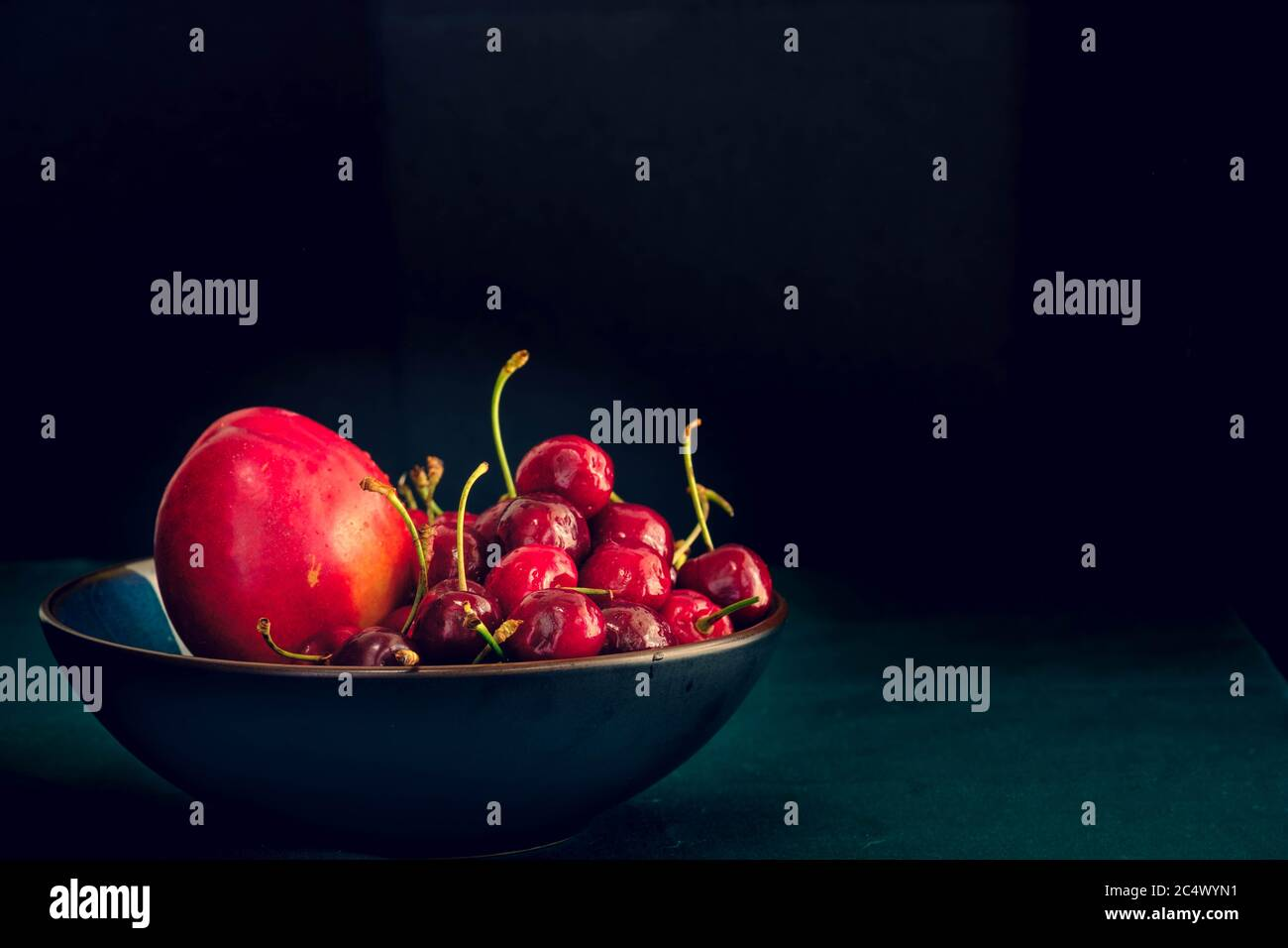 Bowl of cherries and nectarine on dark background, with negative space Stock Photo