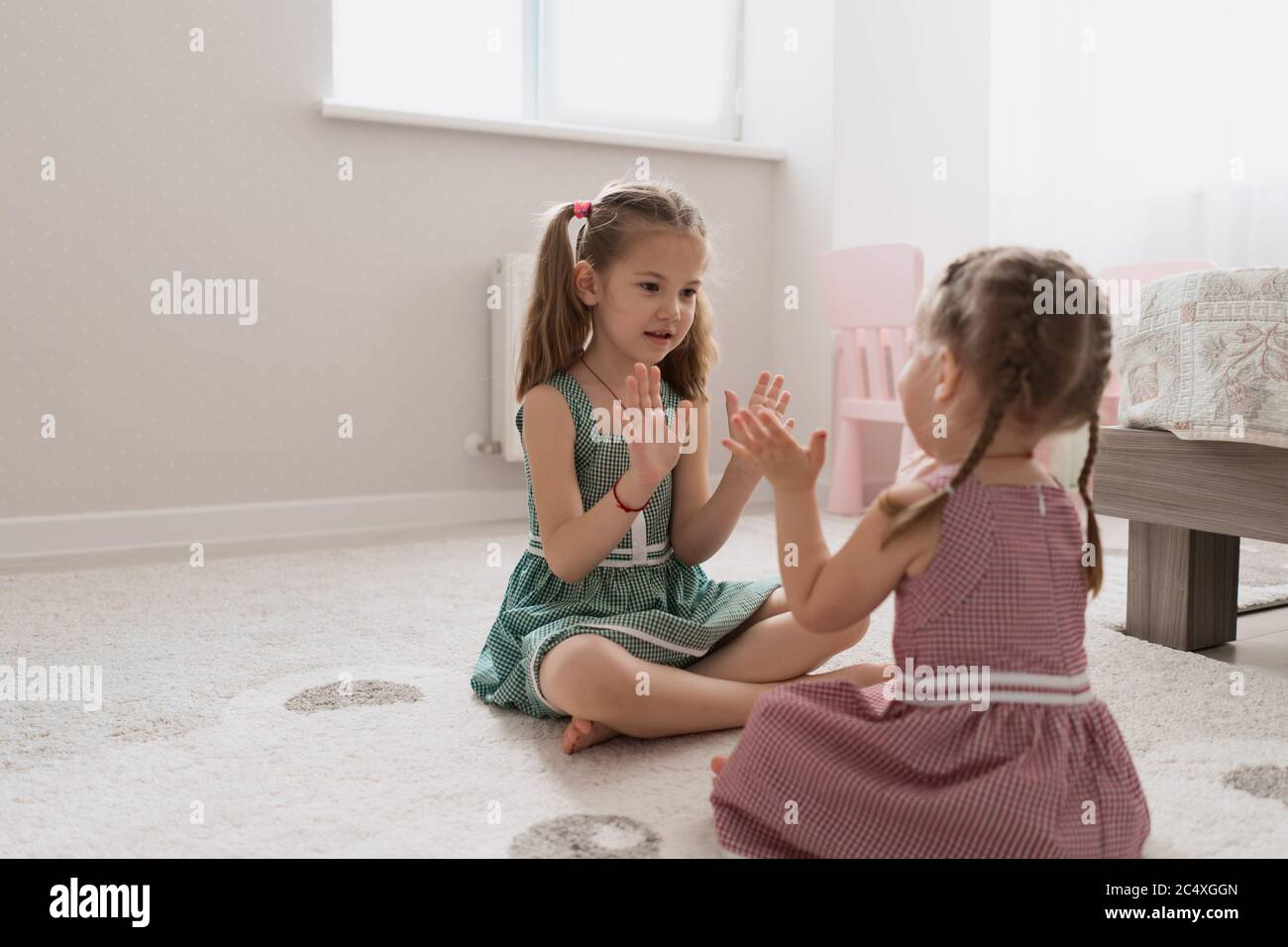 Cute little sisters playing together sitting on the carpet in identical dresses different colors in a room with lots of light Stock Photo