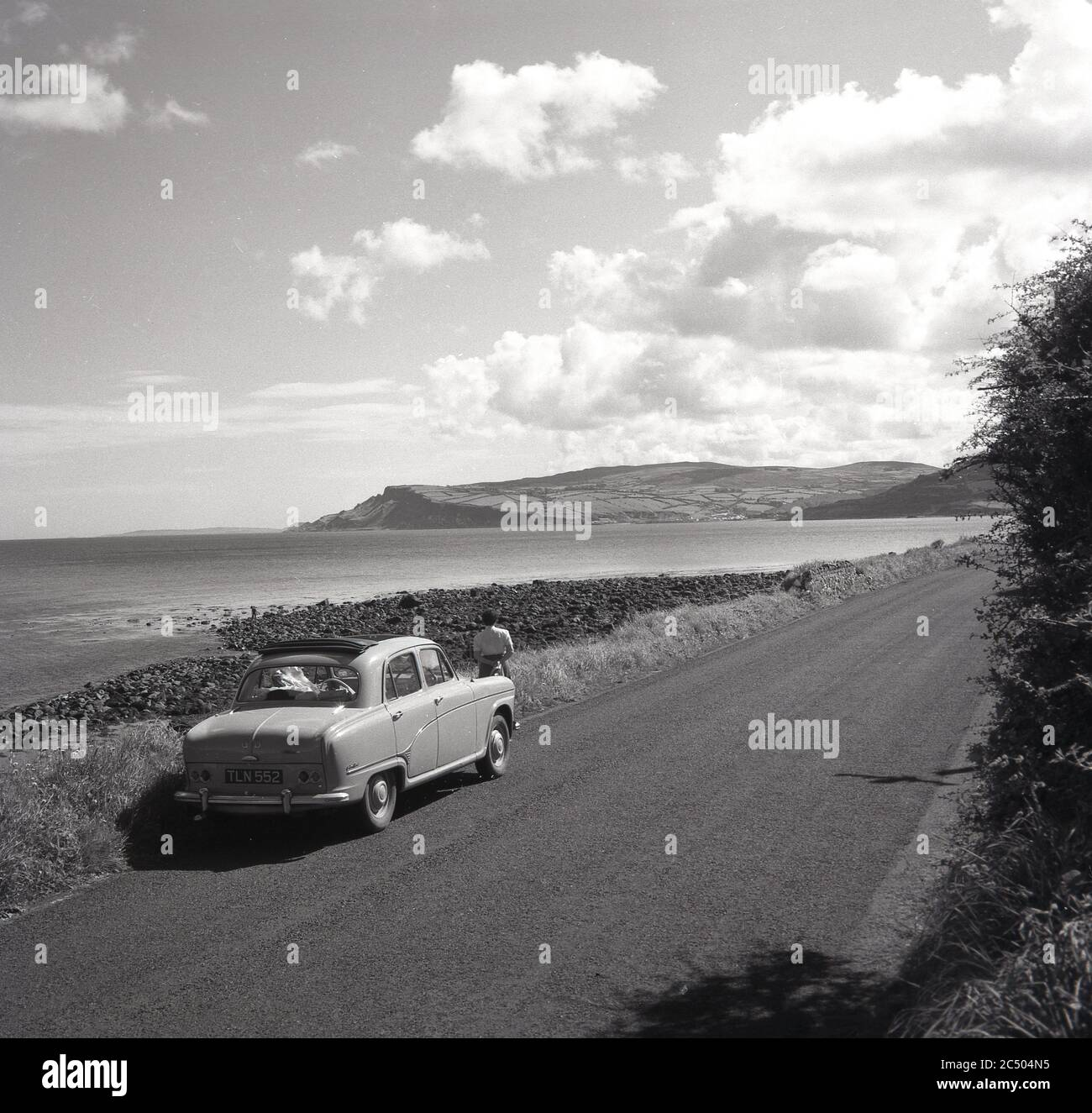 1950s, historical, a lady standing by her car of the era parked on a road on the famous Causeway coastal route, Co. Antrim, Northern Ireland, one of the most famous scenic driving routes in the world. From Belfast to Londonderry (Derry) the winding road takes in the rugged and spectacular coastline of Northern Ireland. Stock Photo