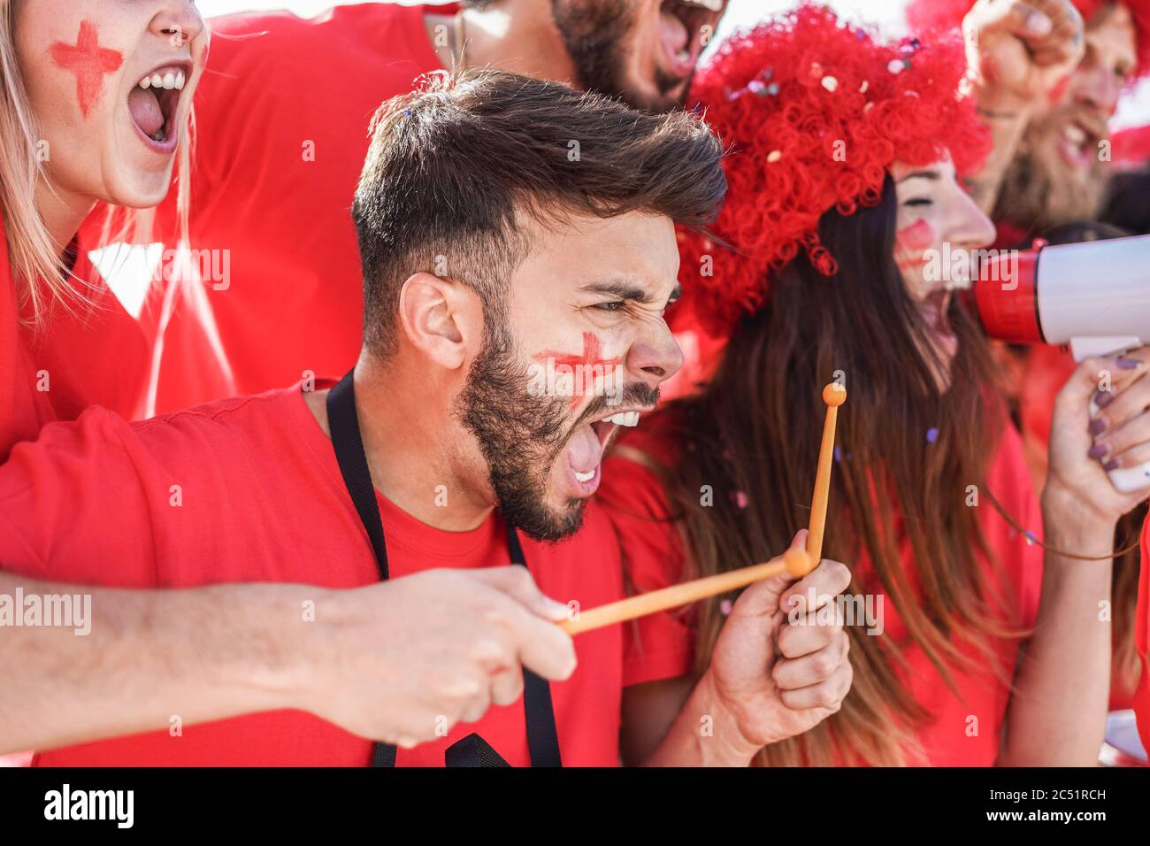 Red sport fans screaming while supporting their team out of the stadium - Football supporters having fun at competion event - Champions and winning co Stock Photo