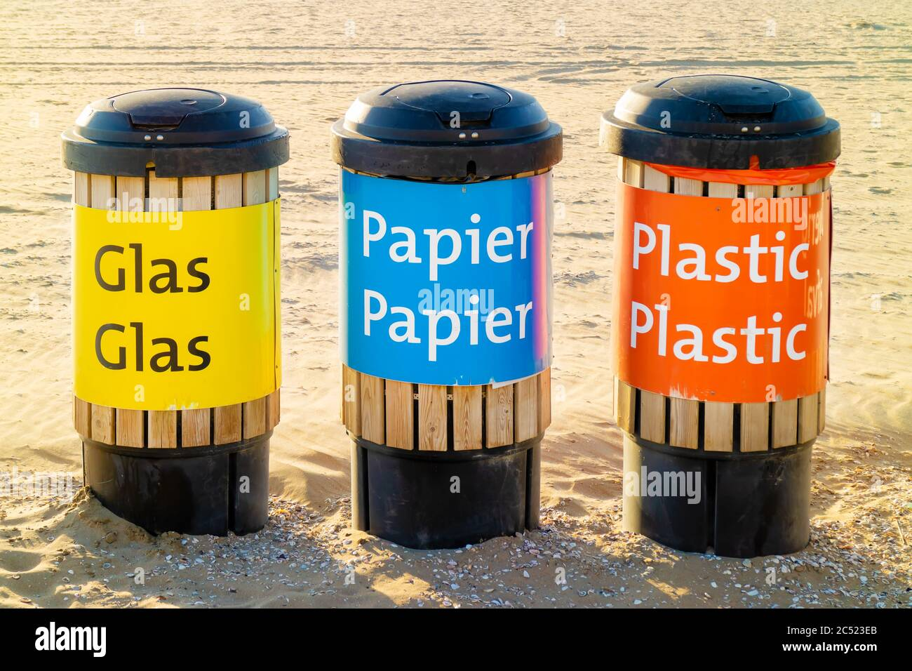 Dutch recycle waste bins for glass, paper and plastics on a beach Stock Photo