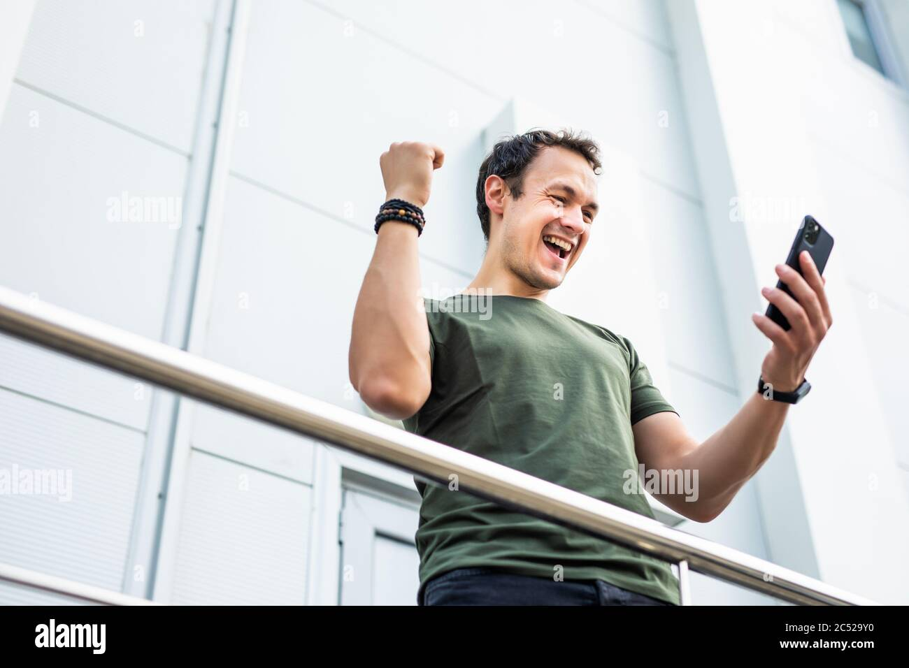 Surprised man holding phone looking at phone shocked by unexpected social media news. Astonished young man amazed stunned by mobile online content out Stock Photo