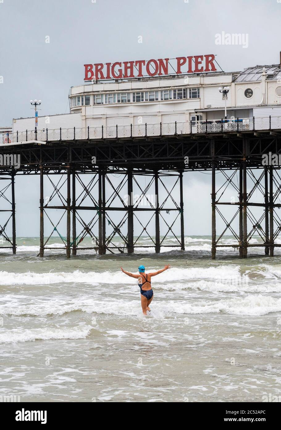 Brighton UK 30th June 2020 - Sea swimmers brave the conditions in Brighton on a wet cold and windy day compared with this time last week when the summer heatwave was beginning with temperatures above 30 degrees : Credit Simon Dack / Alamy Live News Stock Photo