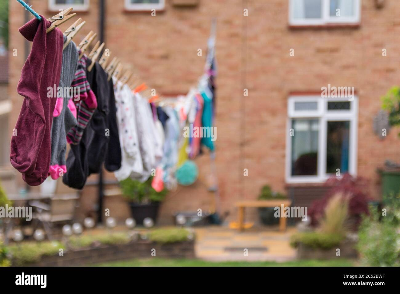 Washing hanging on long line drying in the gusty windy weather. Full length of my garden taken up with washing drying and blowing around end to end. Stock Photo