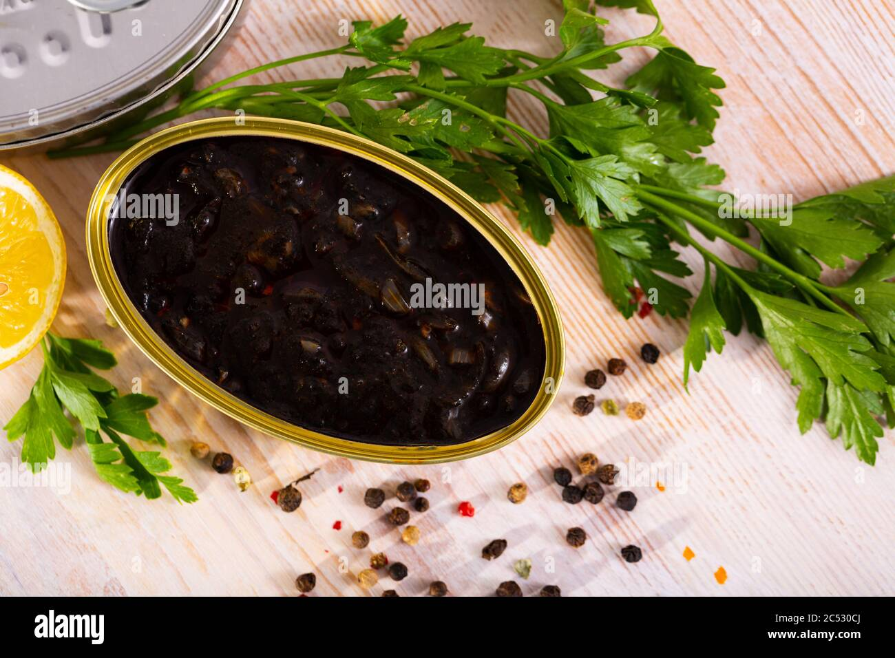 Open can with squid in ink in group of closed cans with seafood, parsley and lemon Stock Photo