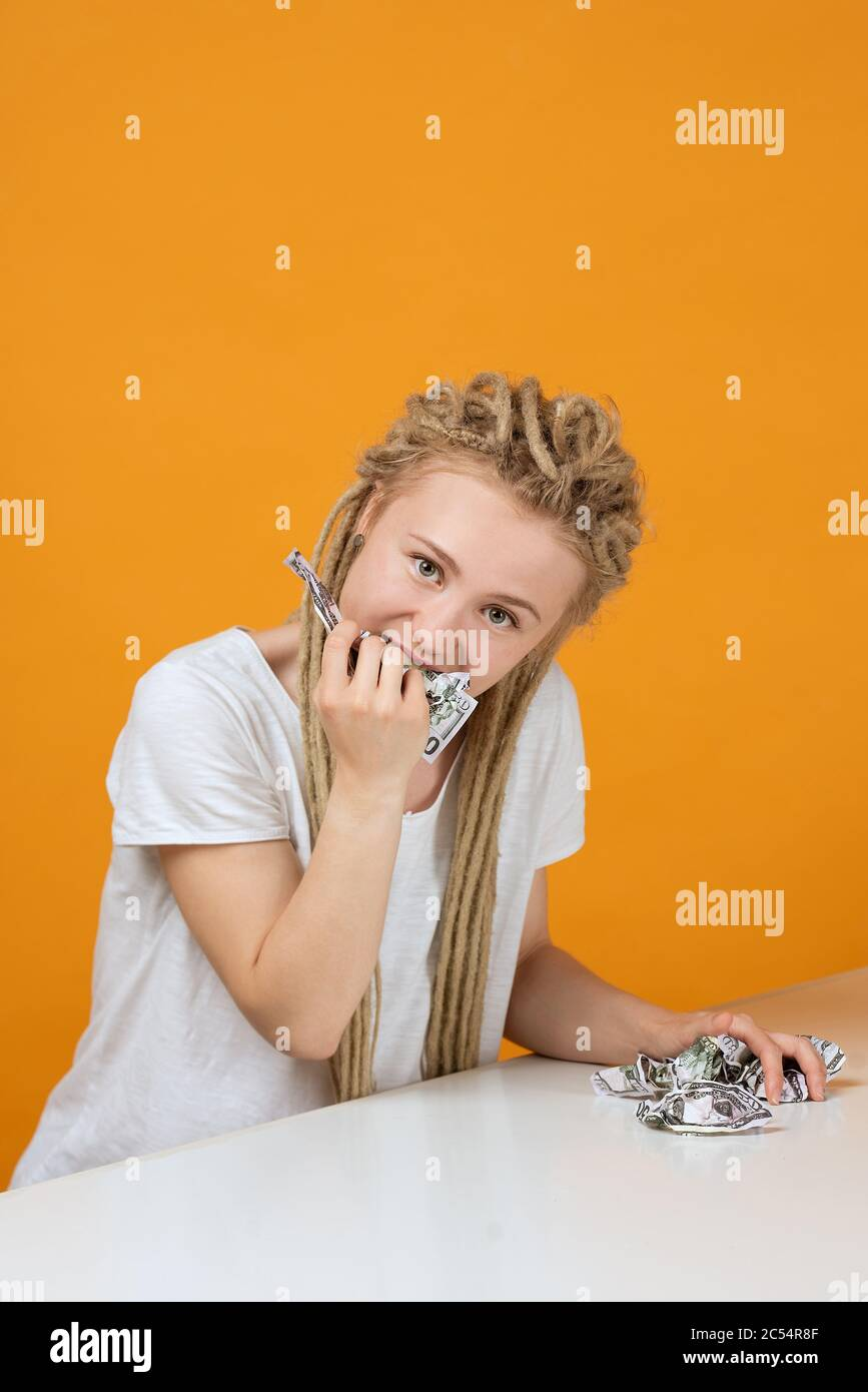 young girl bites off banknote, crumpled money in her hands sits at a white table, emotions on her face Stock Photo
