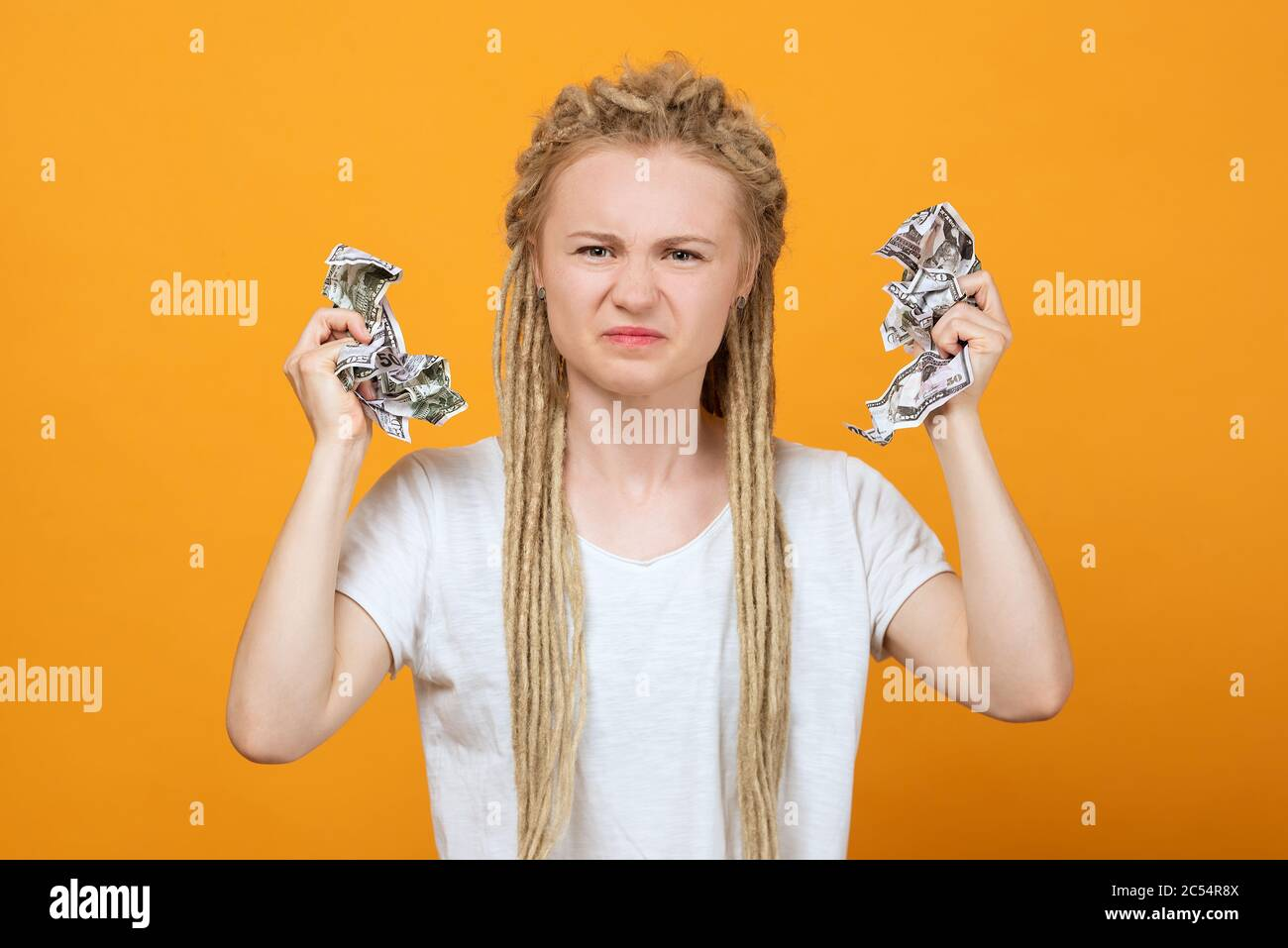 angry and distressed girl holding money in her hands, hair braided in dreadlocks, wrinkled face, Stock Photo
