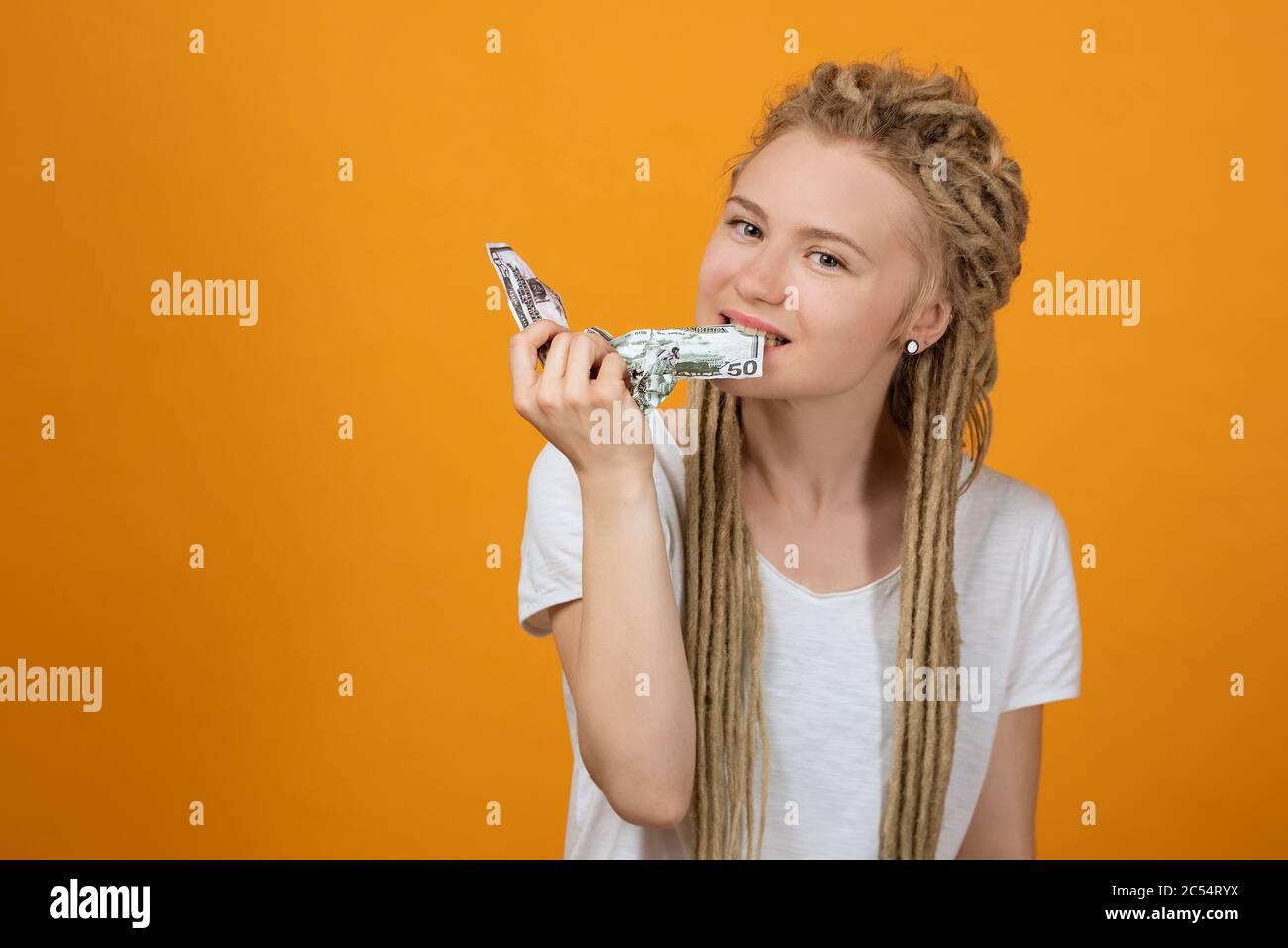 girl with long dreadlocks bites off money, crumpled banknotes in her hands Stock Photo