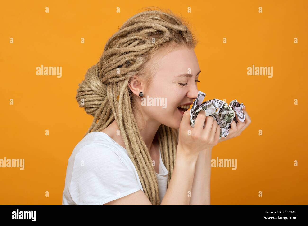 girl holds crumpled money and wants to eat it, playful mood, unusual hairstyle, white dreadlocks Stock Photo