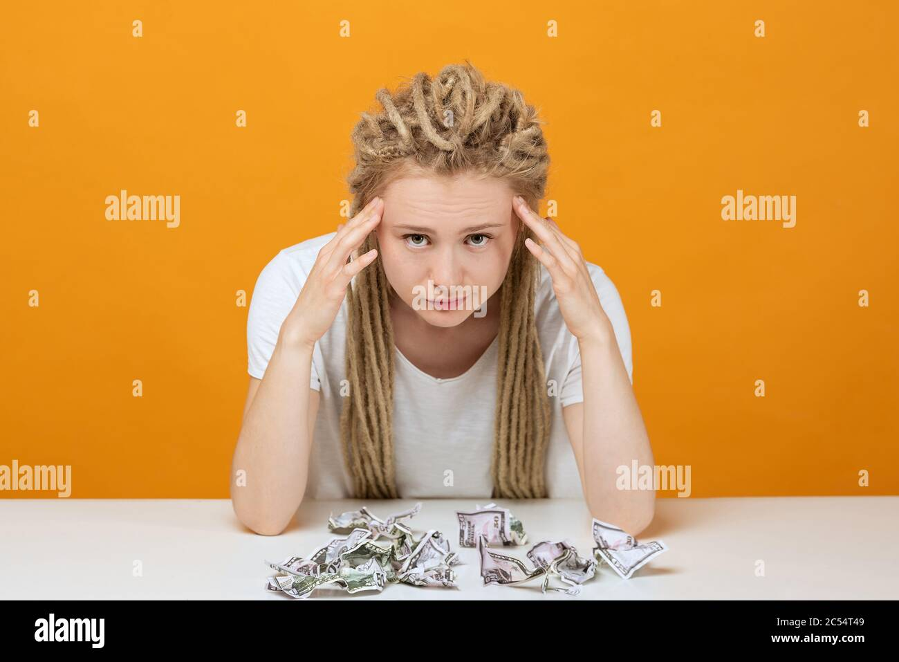girl with financial problems sits at table, hands holding his head, crumpled bank notes lie on the table Stock Photo