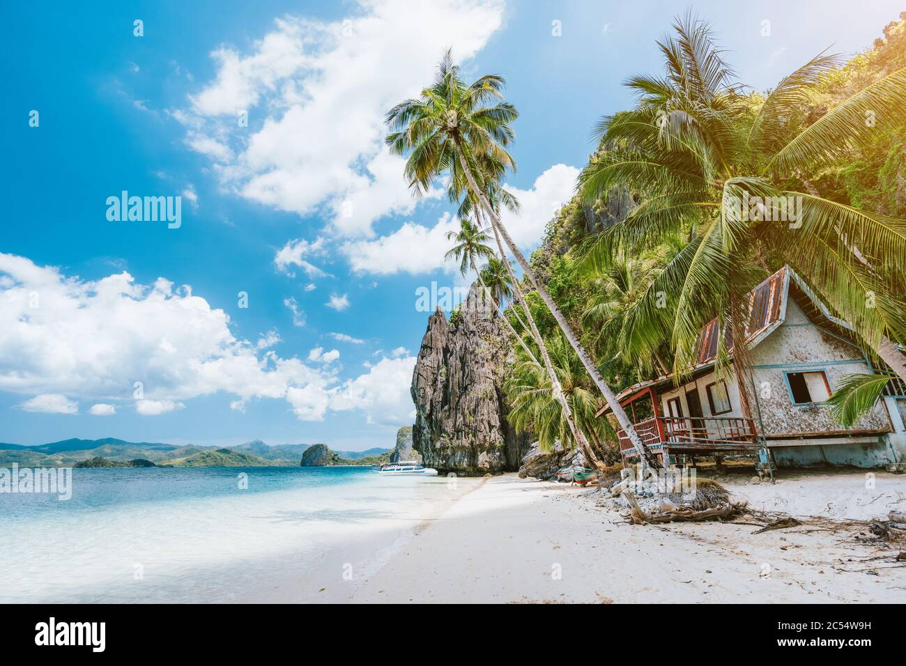 Vacation holiday on Palawan - El Nido island hopping tour. Lonely deserted hut under palm trees, cliff rocks in background. Stock Photo