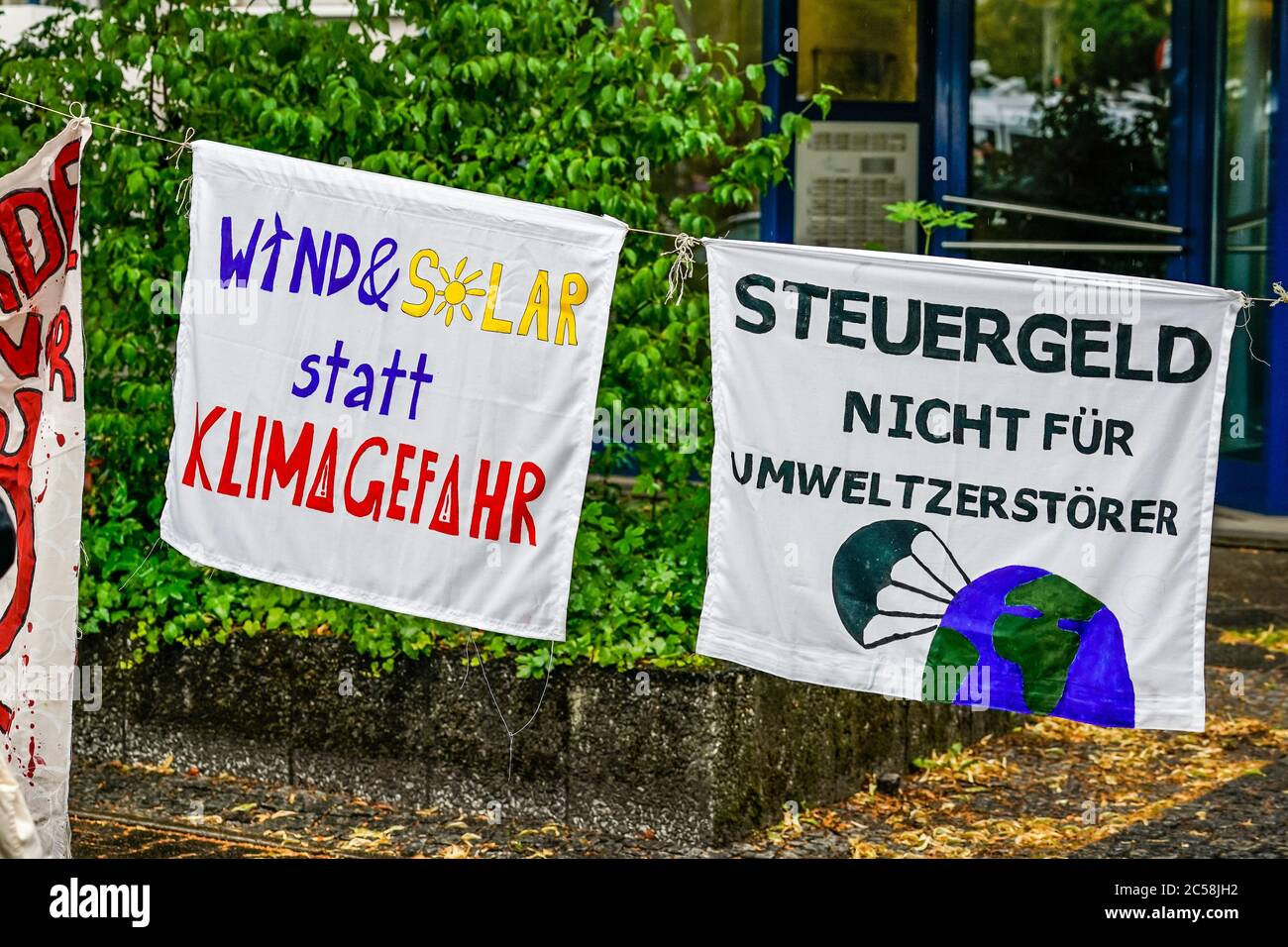 """01.07.2020, Berlin, while in the Klingelhoferstrasse the CDU headquarters were blocked by Greenpeace activists with black cloths, another coal demonstration took place in front of the Willy-Brandt-Haus, the party headquarters of the coalition partner SPD. With this campaign, the demonstrators want to draw attention to dirty coal deals by the grand coalition with the coal industry, which are questioning compliance with the Paris climate agreement. Photo of two banners with the inscription: """"Wind & Solar instead of climate risk"""" and """"Tax money not for environmental destroyers"""".   usage worldwide Stock Photo"""