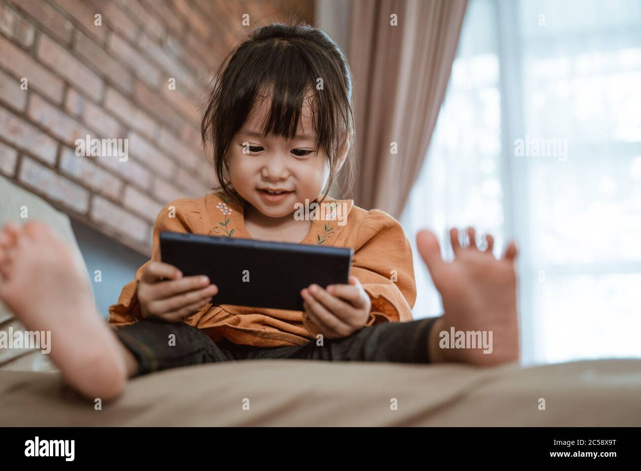 little girl laughed happily when holding a phone to see the child's video Stock Photo