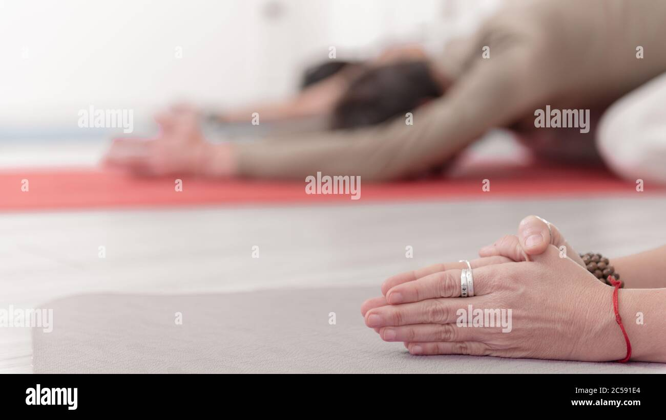 Close-up of feminine and masculine arms during meditation.  Shashankasana position. Rabbit Pose. Seguence of Surya namaskar. Greeting to the Sun. How Stock Photo