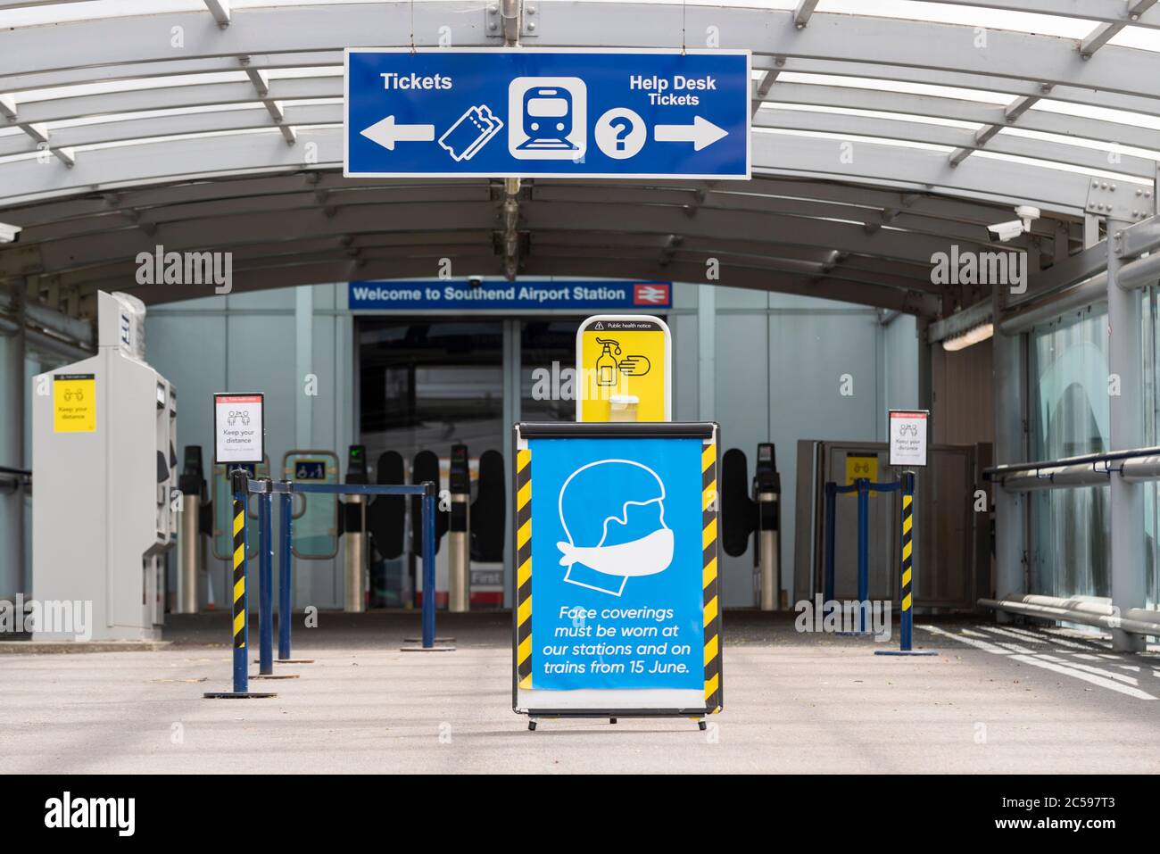 Entrance to Southend Airport railway station with signs related to COVID-19 Coronavirus health pandemic. Face coverings must be worn. Hand sanitiser Stock Photo