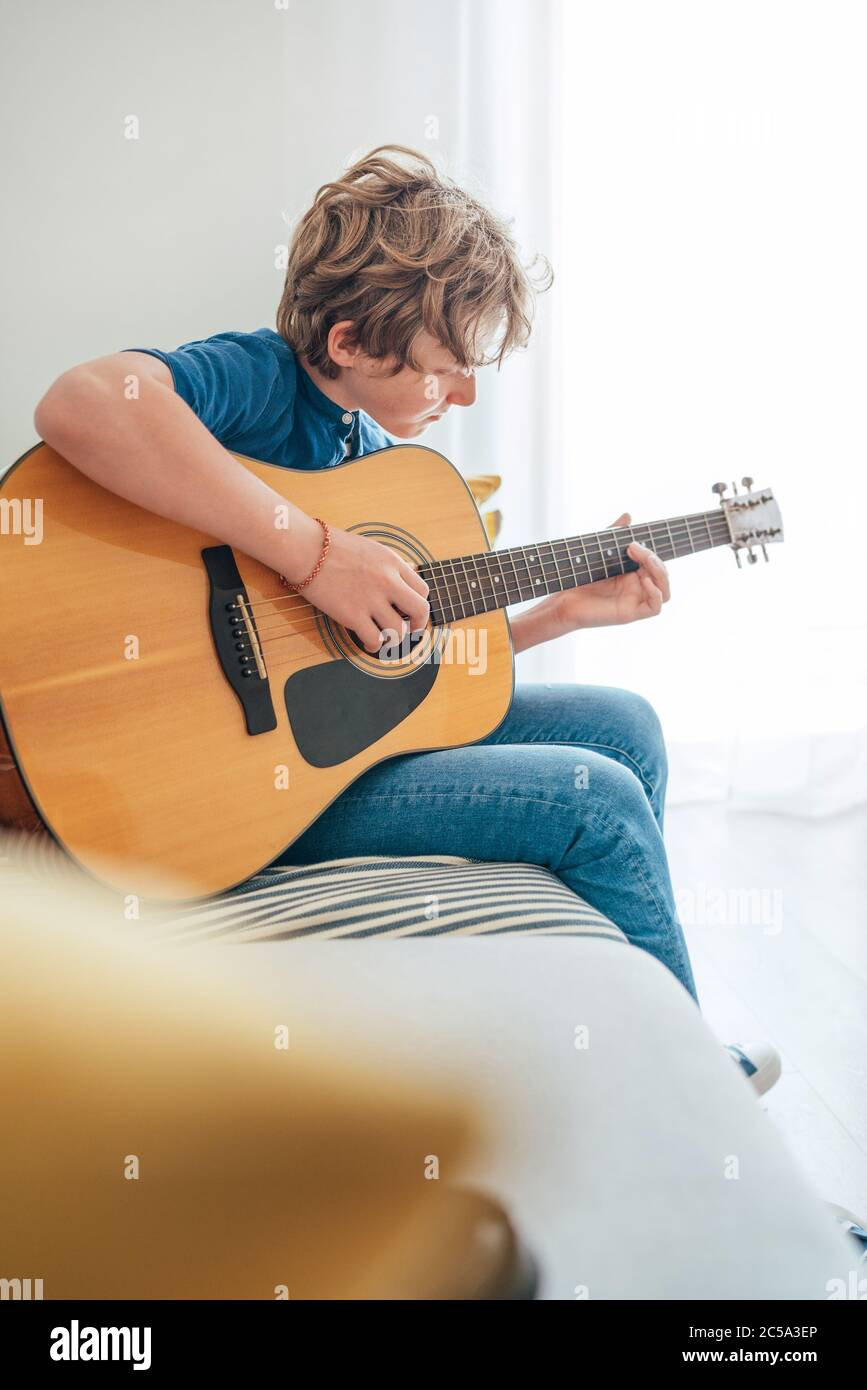 Preteen boy playing acoustic guitar dressed casual jeans and shirt sitting on the cozy sofa at home living room. Music education concept image. Stock Photo