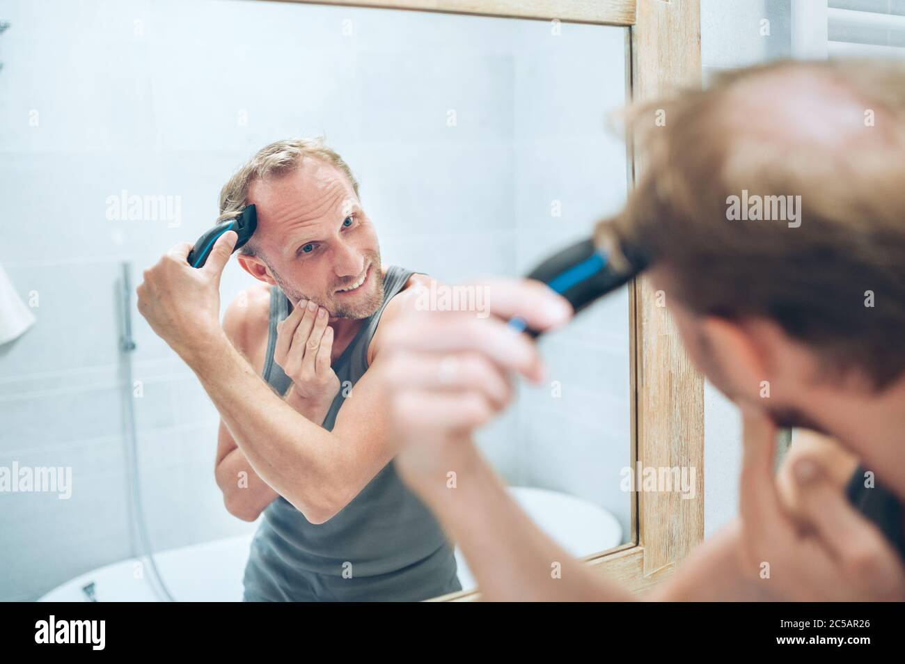 Body and skincare treatment concept. Smiling Man making new style haircut trimming a hairs using an electric rechargeable Trimmer looking in bathroom Stock Photo